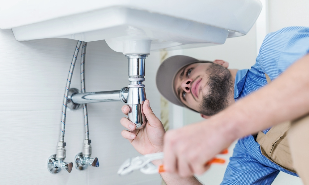 plumber fixing sink pipes